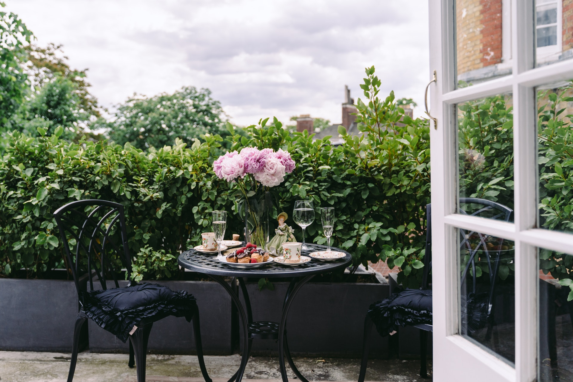 french flowers pink peonies on a table on a balcony
